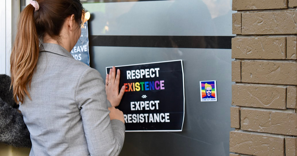 Queer Amnesty Ireland: woman holds poster up with the words respect existence or expect resistance