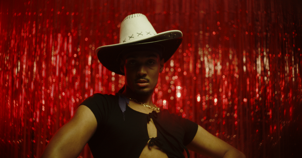 ballroom dancer wearing a hat posing in front of red background