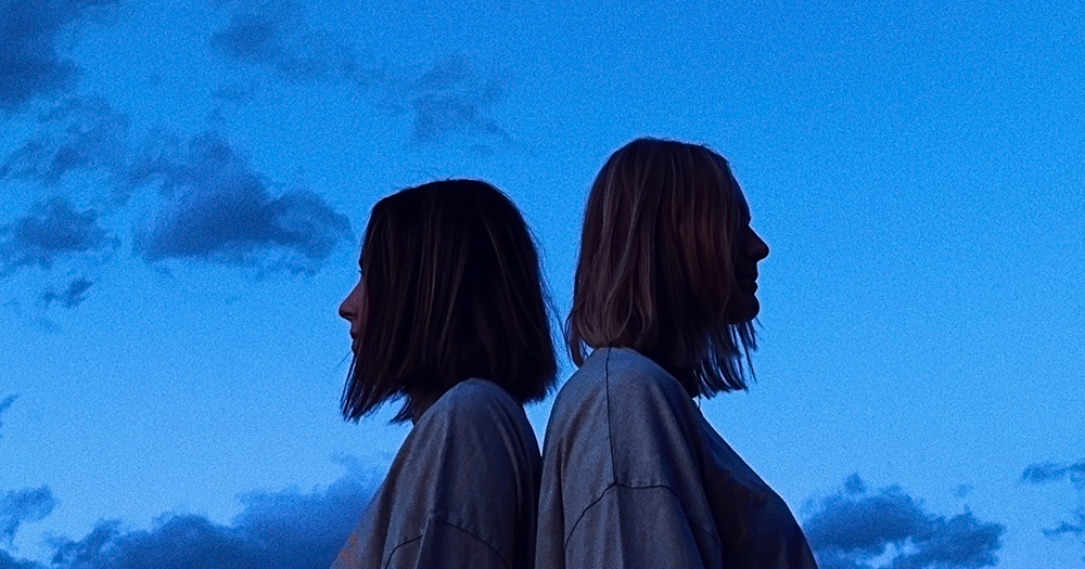 "Two women with their backs against each other. Behind them a dark blue sky. In this piece, Christine Allen explores the complexity of dating someone ""out of your league"""