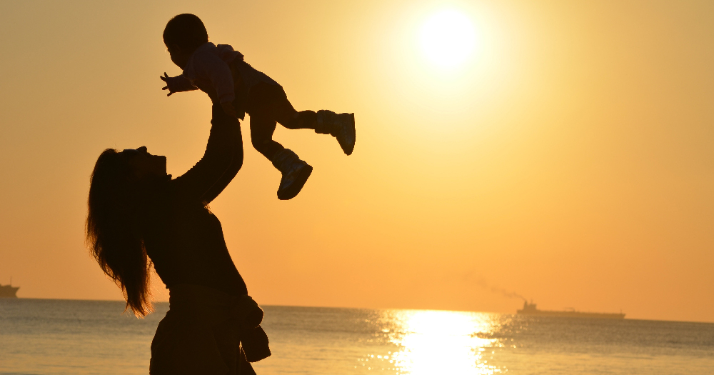 publicly funded IVF feminine person holding a baby in the air is sillouetted against a sunset on a beach