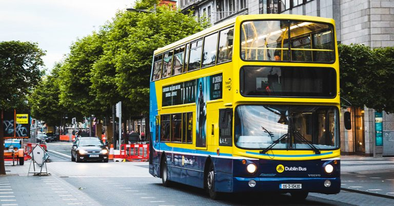 A yellow bus drives down a city street