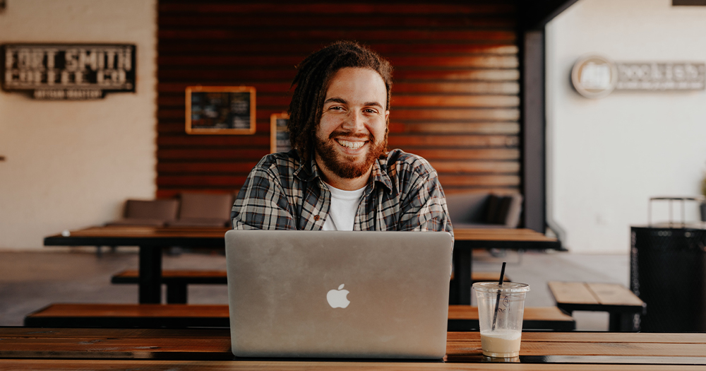 A smiling bearded man sits in front of a laptop