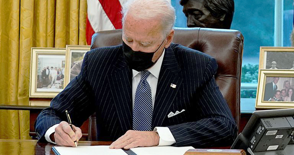 President Biden signing papers, wearing a facemask in the White House, he recently overturned the trans military ban