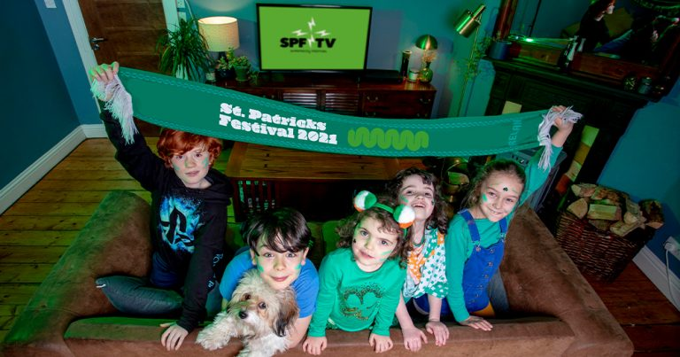 Five children hold up a green banner in their sitting room