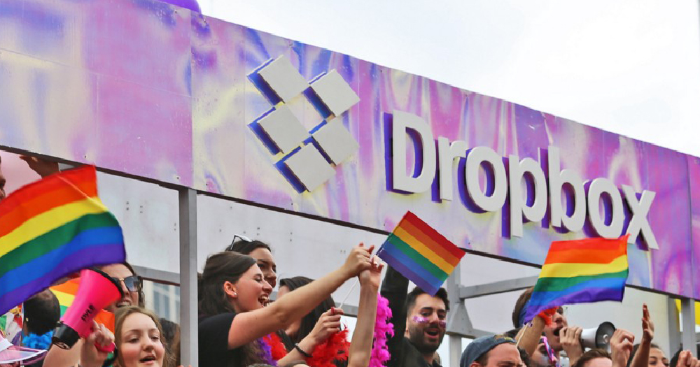 People with rainbow flags standing in front of a Dropbox sign