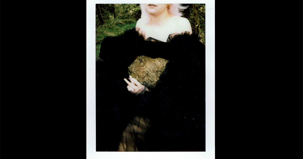 A polaroid of a woman holding a rock