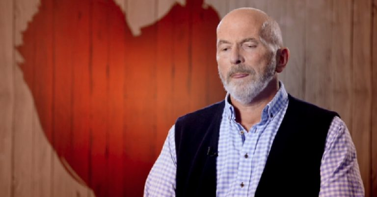 An older bald man getting emotional