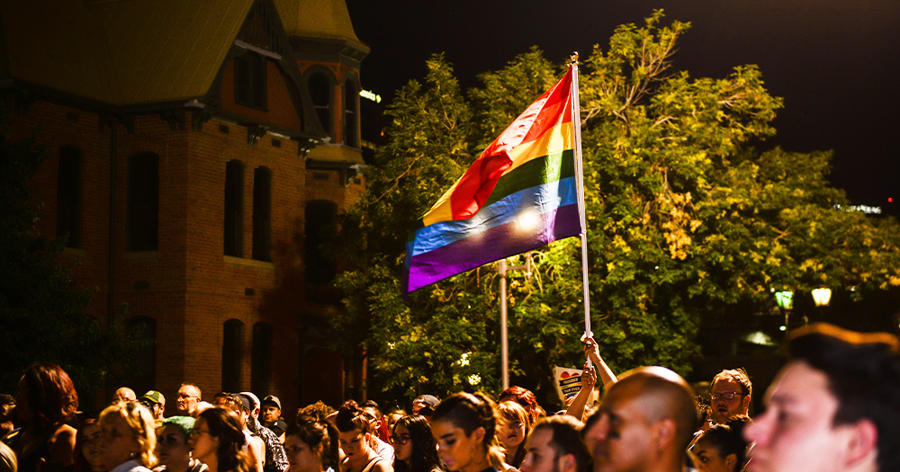 A group of protestors at night with a rainbow flag held high