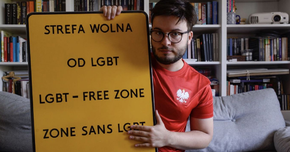 A man holds up a sign with Polish writing