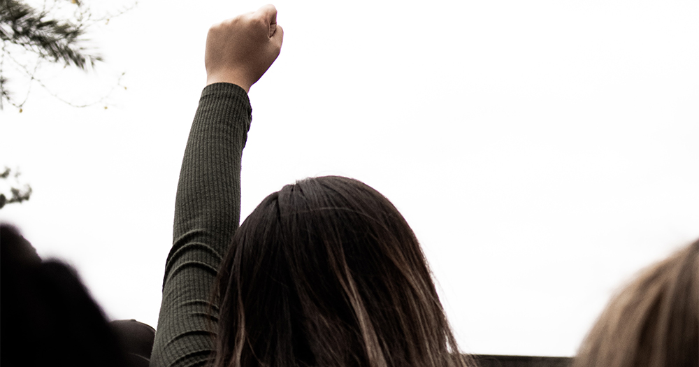 a woman holds her fist in the air