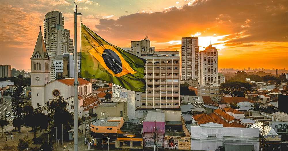 A city with the Brazilian flag in the foreground