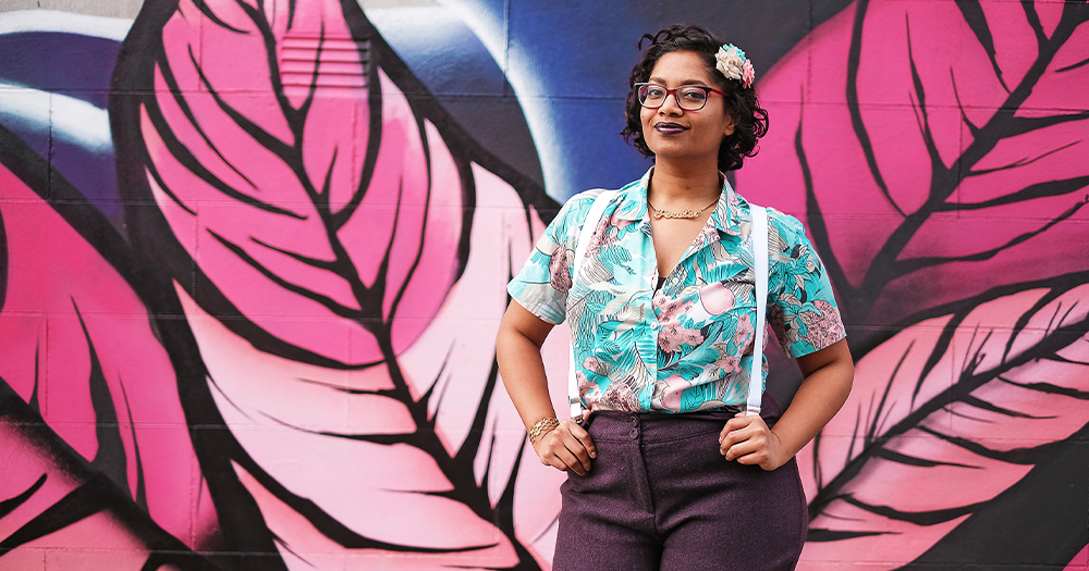 A smiling woman poses in front of a huge painted mural
