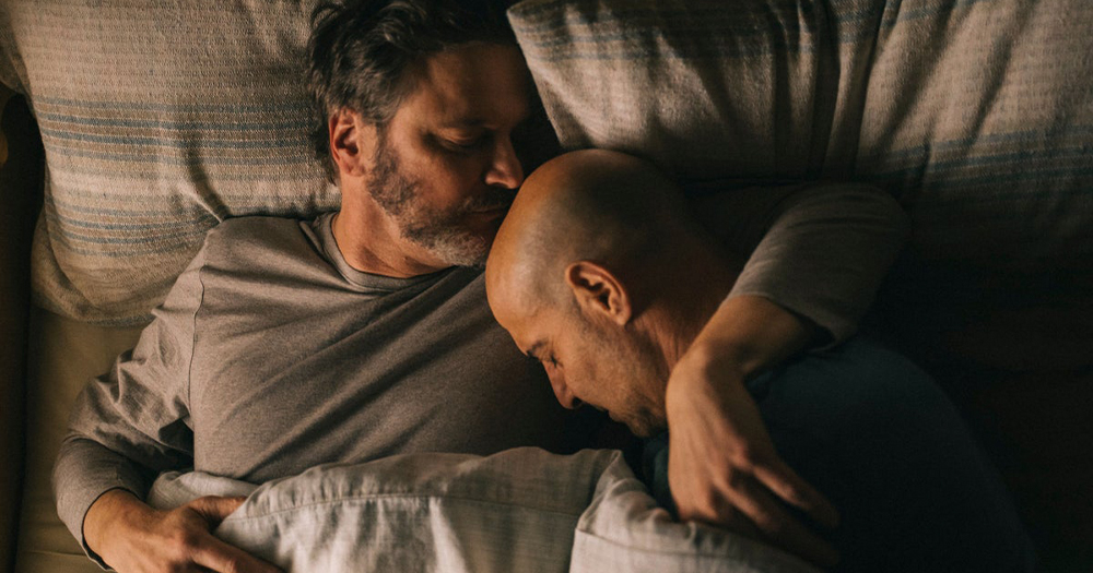 Two middle aged men embracing in bed