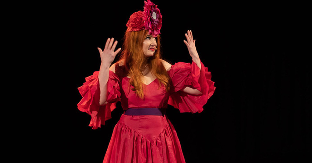 A flamboyantly dressed woman on a stage