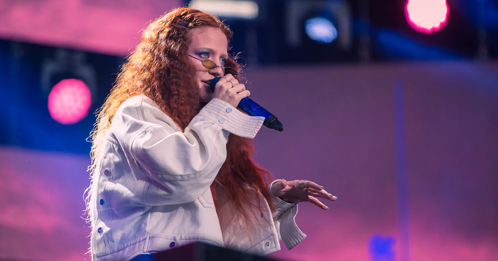 Jess Glynne on stage, holding a microphone, with purple lighting behind her