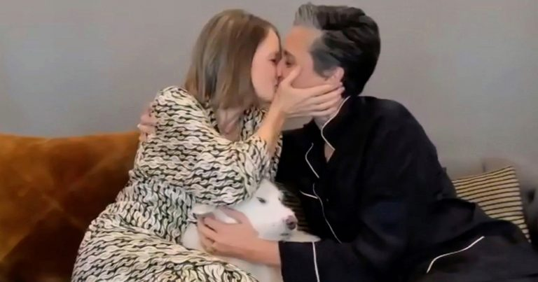 Two women kissing with a dog sitting between them