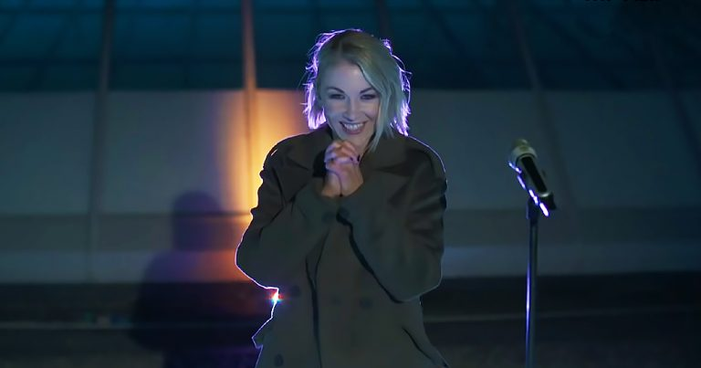 A woman outdoors at night by a microphone