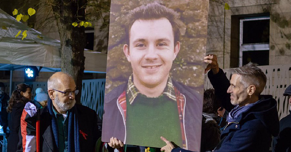 People holding up a large photo/poster of activist mark ashton