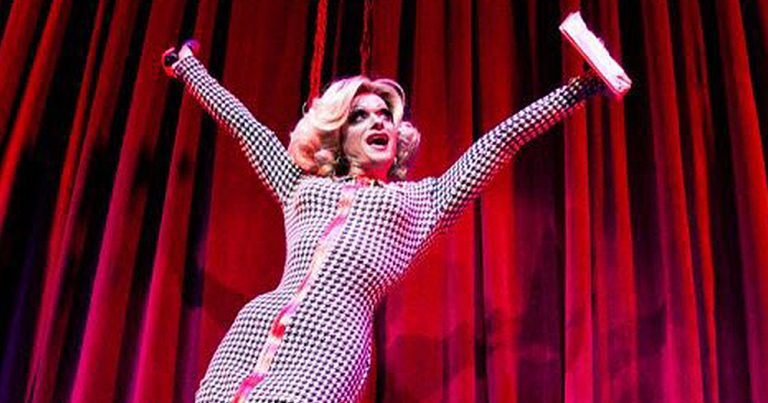 A drag queen throwing her arms wide