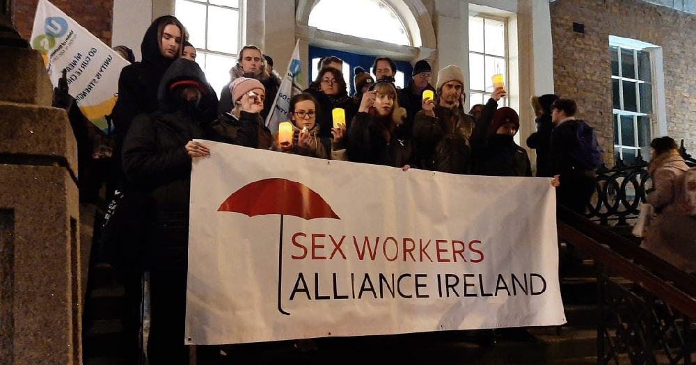 A group of people outside holding a banner supporting sex workers