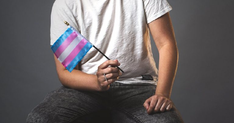 The torso of a man holding a trans flag