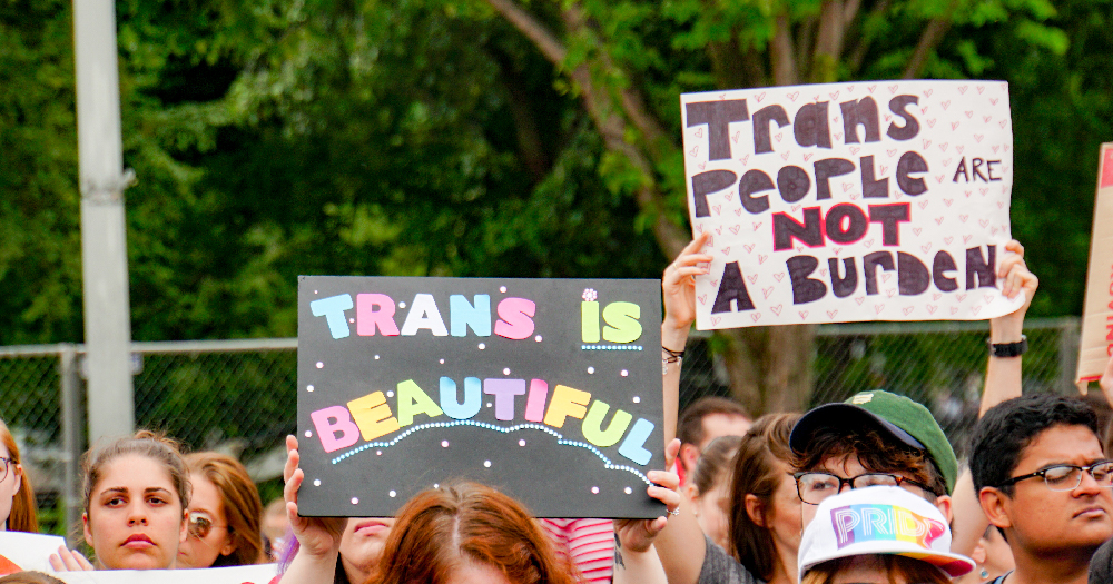 A group of people holding up signs in support of the trans community