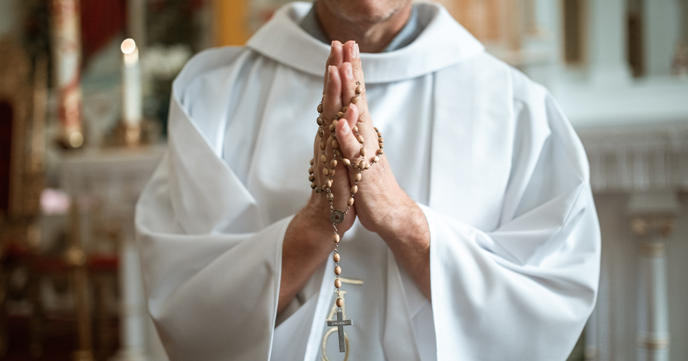 A priest's hands holding rosary beads
