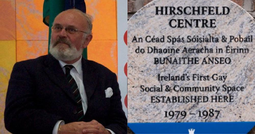 An older gentleman posing beside a memorial plaque