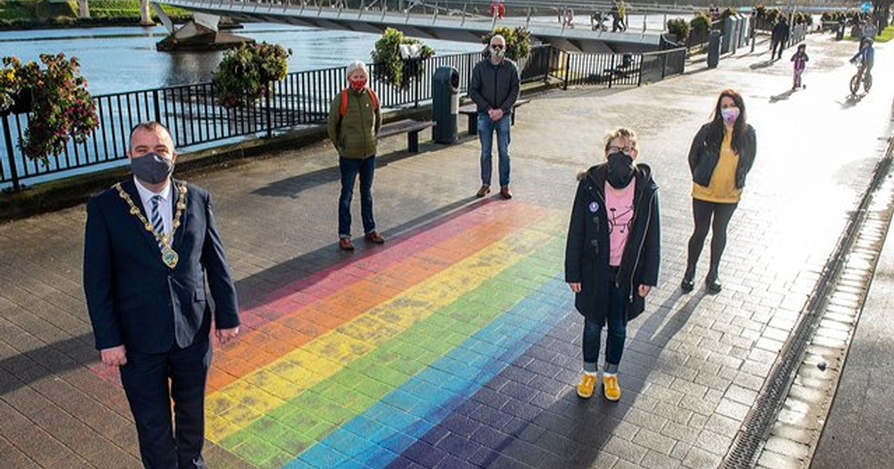 A group of masked people standing beside a rainbow painted on the ground