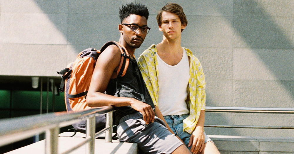 Two young men lean against a railing looking at the camera