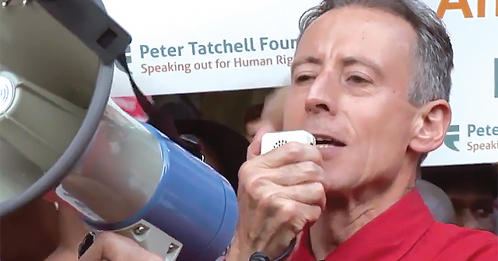 A middle aged man talking into a megaphone at a rally