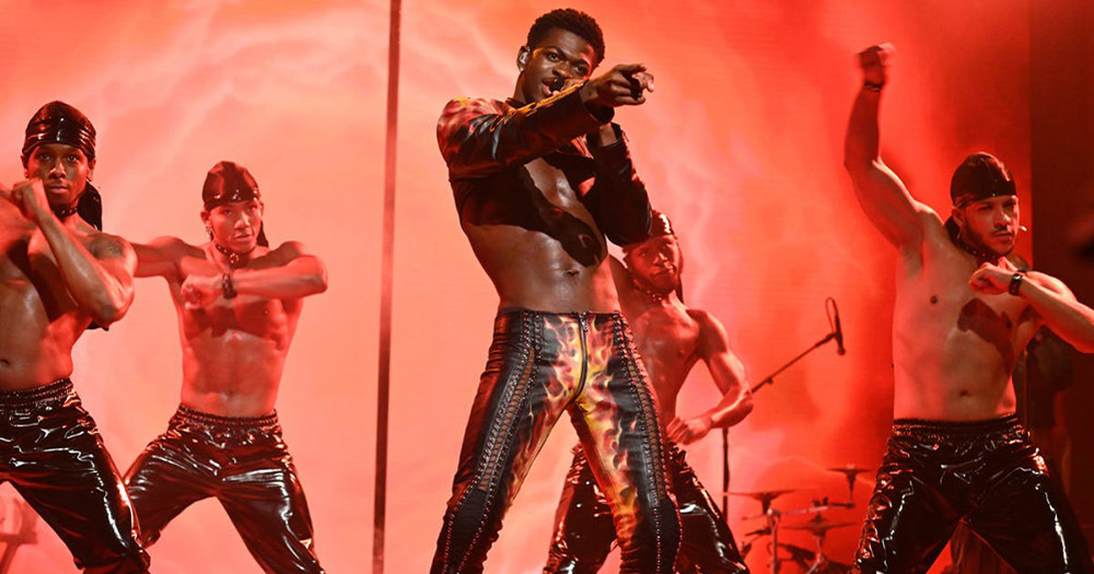 A man singing in leather pants surrounded by muscular dancers