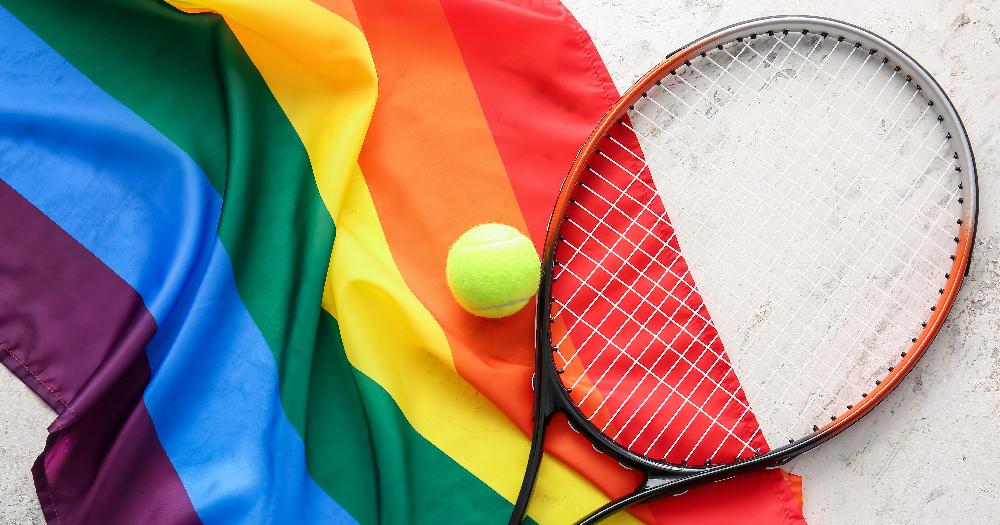 A tennis racket and ball on top of a rainbow flag