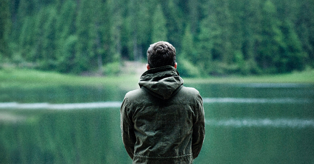 lgbtq isolation photo of man wearing hooded jacket in front of body of water