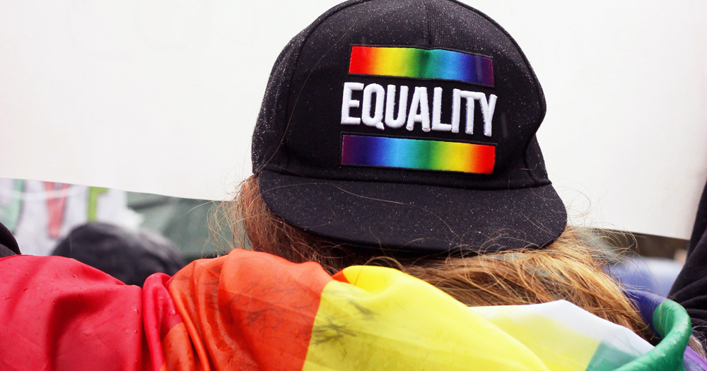 A person with long hair wearing a cap reading 'equality'