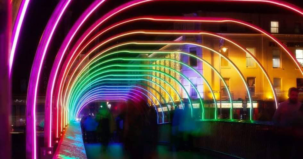 Rainbow lights cover a bridge