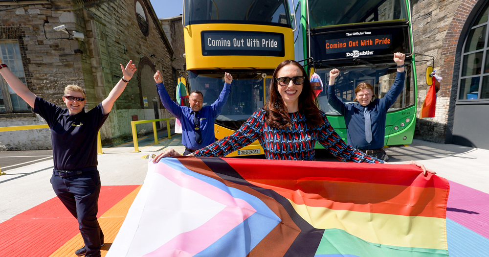 From Coming Out with Pride campaign: A group of people holding the rainbow flag, in the background 2 buses.