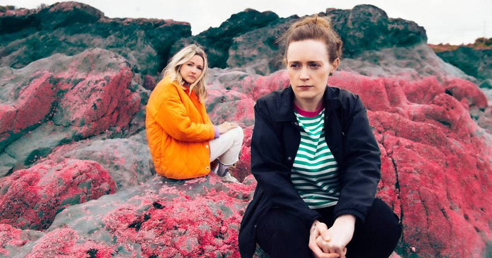 Two women sitting on rocks