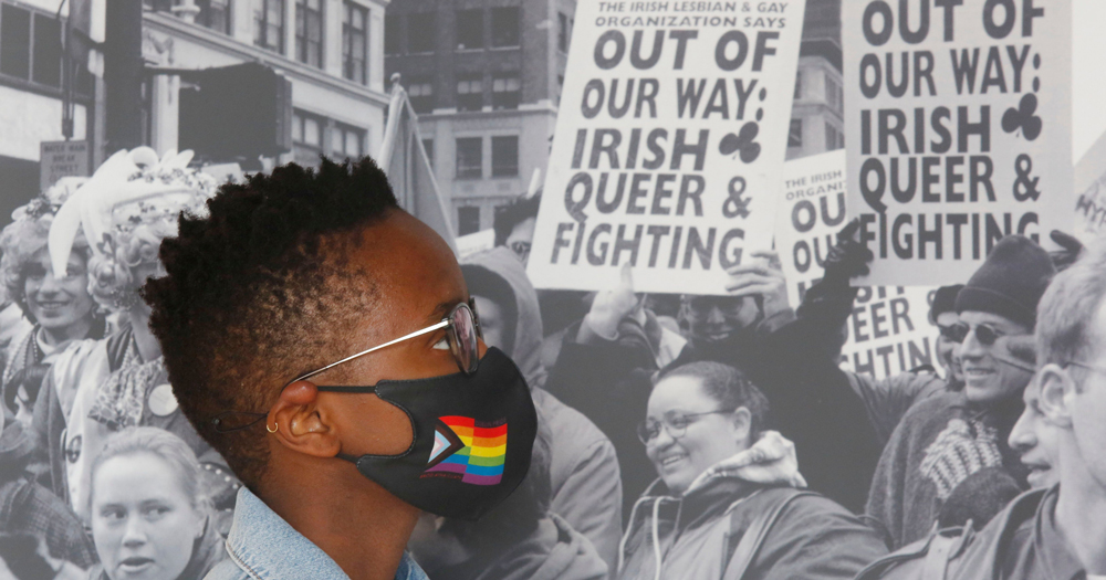 A woman wearing a rainbow mask, in the background a black and white photo featured in the out in the world exhibition