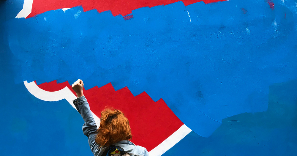 Woman holding her fist in front of a partially covered Repeal mural. The 'how the yes was won' podcast will explore the movement to repeal the 8th amendement in Ireland.