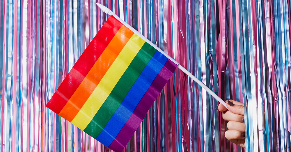 A hand holding a rainbow flag emerging from tinsel curtains