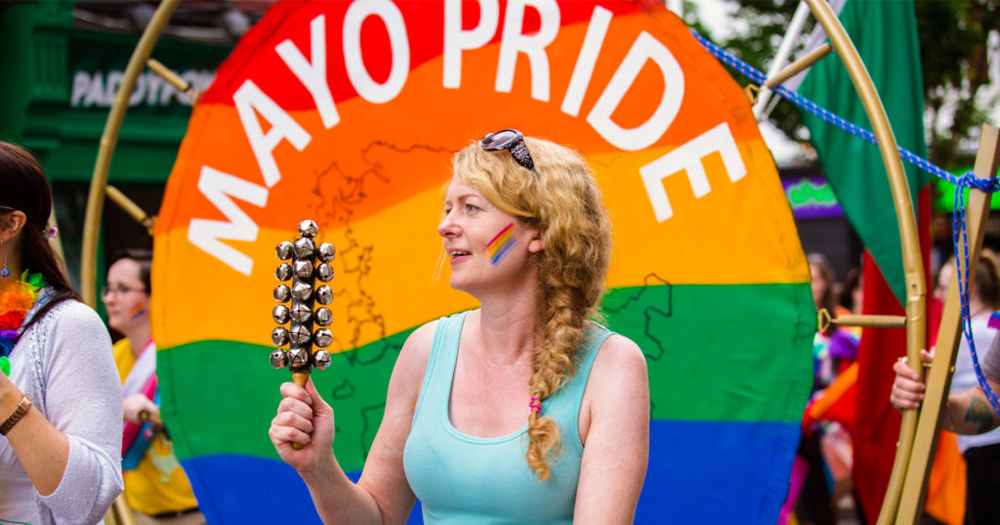 A woman shaking a musical instrument in front of a Pride flag