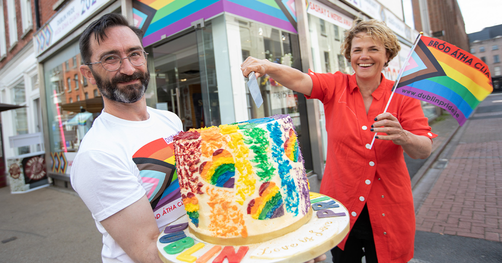 A man holds a rainbow cake while a woman cuts into it