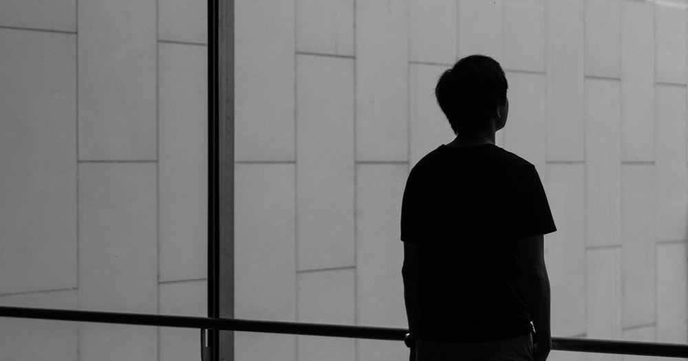 Silhouette of a young person looking outside the window. A new survey has shown that queer youth in Ireland face increased mental health struggles over lockdown