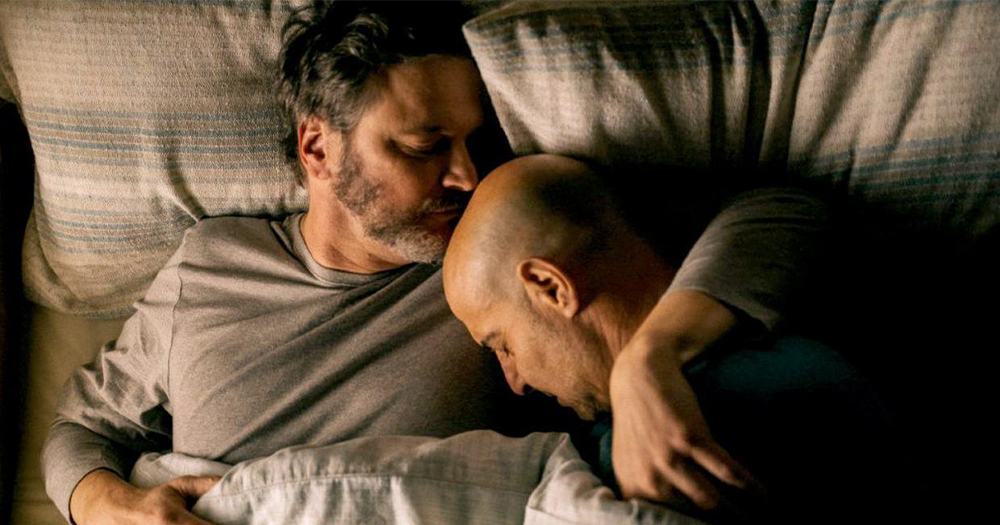 Two men embrace in bed