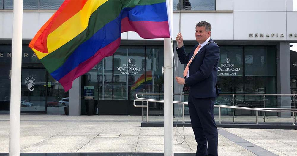 A man in a suit raising a Pride flag outside a building