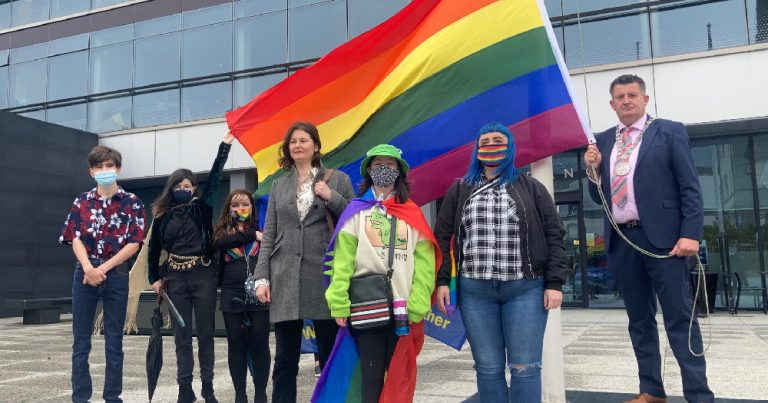 Waterford Pride Flags: group of LGBTQ+ activists pose in front of rainbow flag