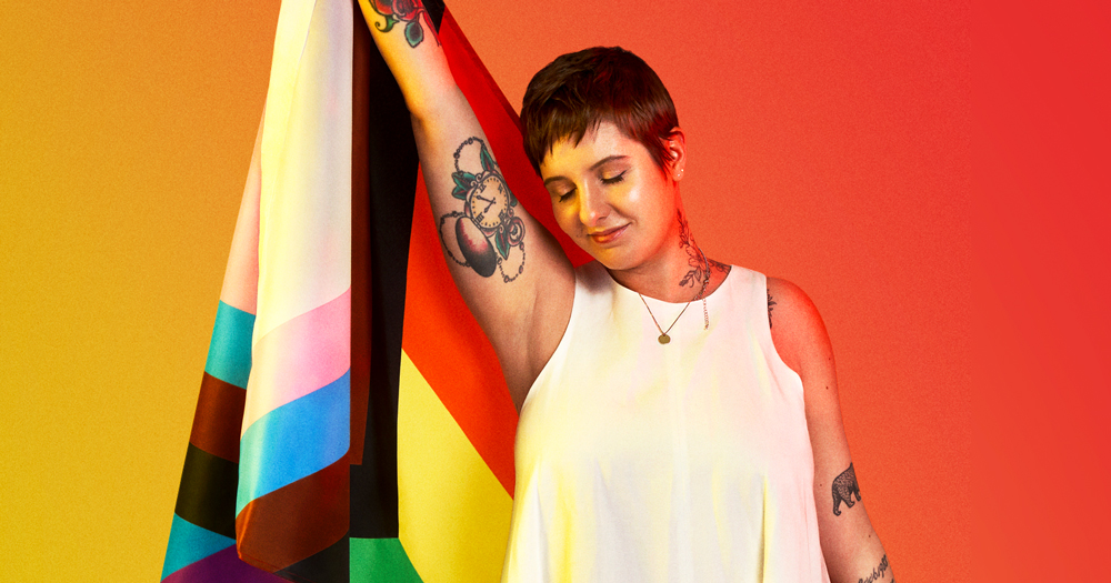 Woman with short hair holding a Pride flag behind her back. Carina talks about finding difficult to coming out about her bisexuality