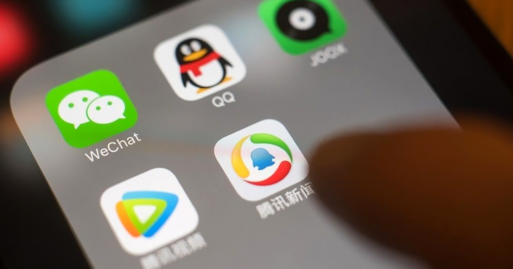 Close-up of a hand holding a smartphone. Several icons appear on the screen, on the top left is WeChat