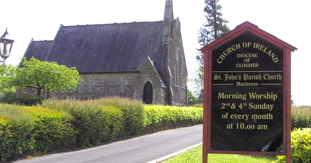 a sign in the foreground lists worship hours for the church in the background - Church of Ireland cleric rejects claims that they are homophobic
